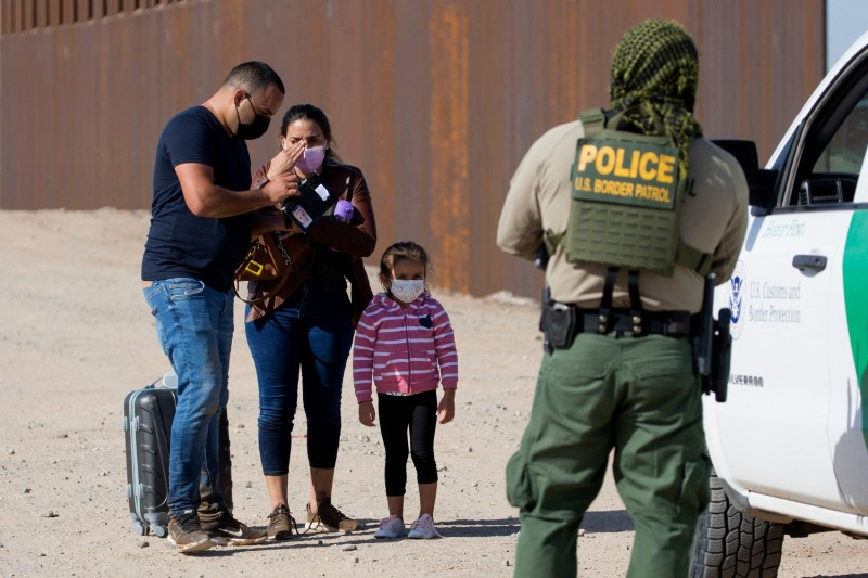 Migrants prepare documents to show the border patrol agents.