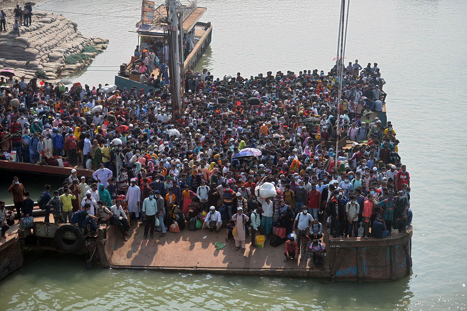 People crowd together as they wait to board a ferry in Bangladesh