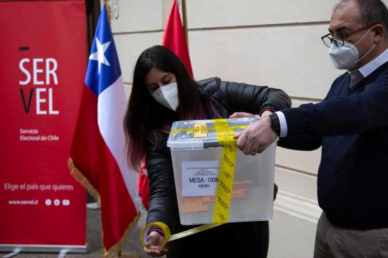 An election service worker seals a ballot box in Santiago, Chile.