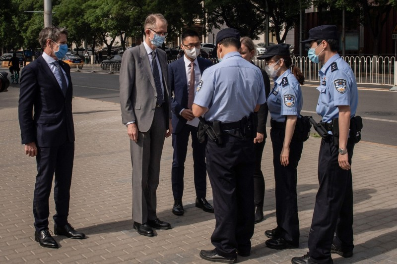 A Chinese police officer checks the ID card of Australian Ambassador to China Graham Fletcher (second left) as he arrives at the Beijing Second Intermediate People's Court before the trial of the Australian academic Yang Jun on espionage charges in Beijing on May 27.