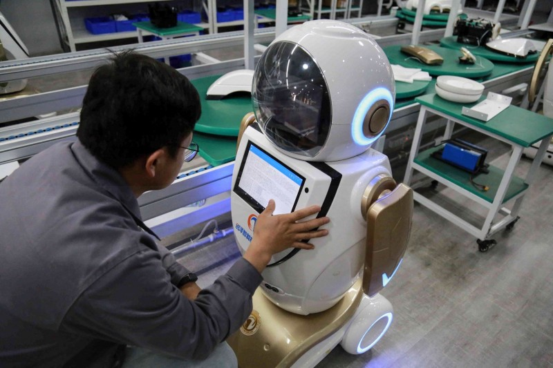 A worker checks a robot in China.