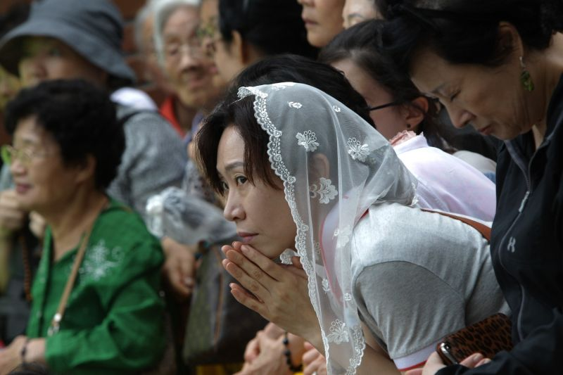 Korean Catholics attend a Mass for peace and reconciliation outside Myeong-dong cathedral on August 18, 2014 in Seoul, South Korea.