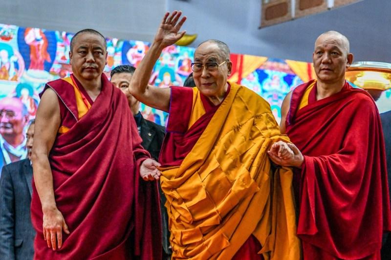 The Dalai Lama waves to the crowd.