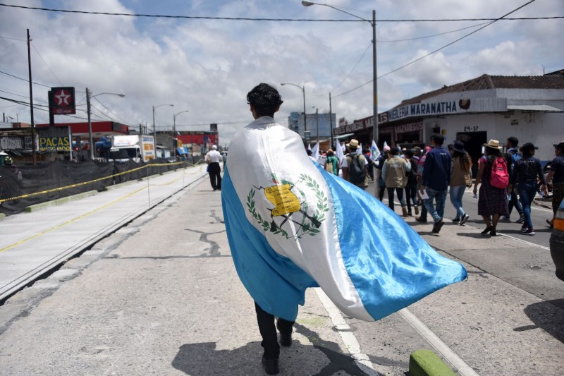A man wrapped in a Guatemalan flag takes part in a march.