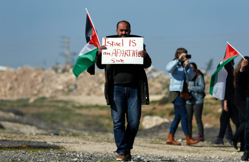A protester carries a sign in the West Bank.