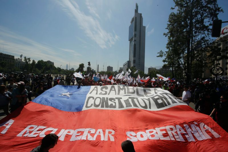 Demonstrators hold a Chilean flag that reads 'Constituent Assembly to recover sovereignty' during the sixth day of protests on Oct. 23, 2019 in Santiago, Chile.