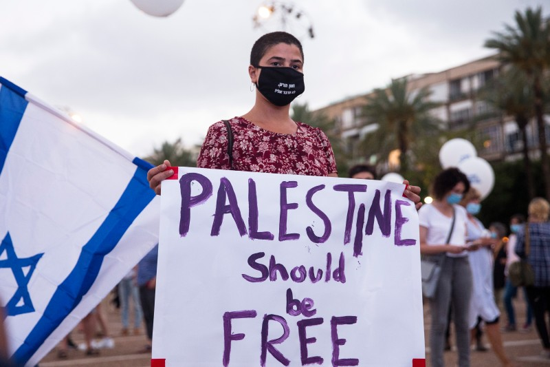 """An Israeli woman holds a sign that reads """"Palestine should be free"""" as she protest against Israel goverment's plan to annex parts of the West Bank on June 23, 2020 in Tel Aviv, Israel."""