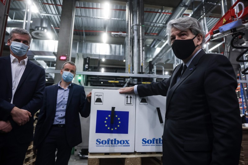 Thierry Breton puts a sticker with the European Union flag on a box containing Pfizer-BioNtech Covid-19 vaccines in Puurs, Belgium on Feb. 22, 2021.