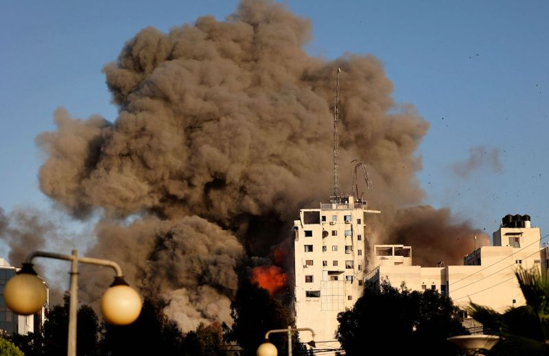Heavy smoke and fire rise from Al-Sharouk tower as it collapses after being hit by an Israeli air strike, in Gaza City, on May 12, 2021.