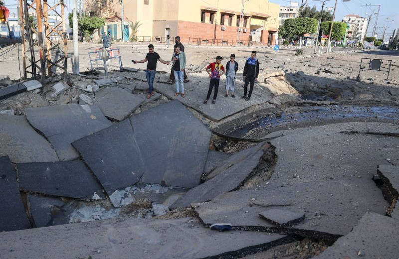 Palestinian youths observe a crater on a main road in Gaza City.
