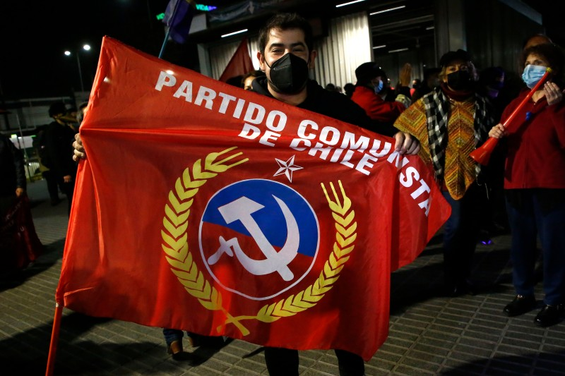 A Chilean holds a flag from the Comunist Party of Chile to celebrate victory after the end Constitutional Convention Elections weekend on May 16 in Santiago, Chile.