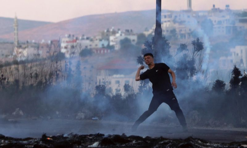 A Palestinian protester throws a stone.