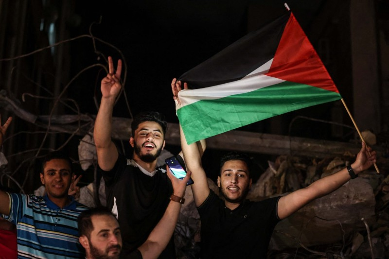 People wave the Palestinian flag as they celebrate a cease-fire.