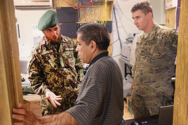 With the help of an interpreter (center), an Afghan National Army doctor (left) speaks with a U.S. Army advisor.