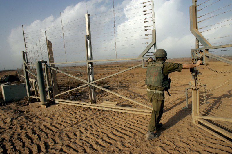 An Israeli army officer opens a gate in the border fence to allow a column of tanks and armored bulldozers to advance into the Gaza Strip to operate against Palestinian militants October 19, 2006 near the southern Israeli Kibbutz of Mefalsim.