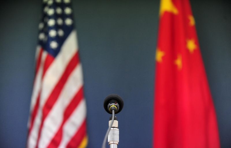 The U.S. and Chinese flags stand behind a microphone.