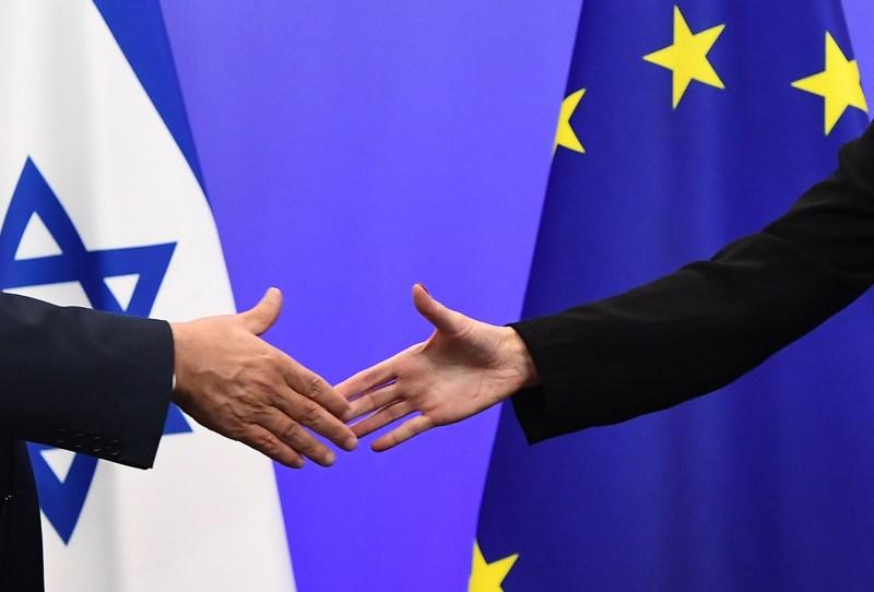 Israeli Prime Minister Benjamin Netanyahu and EU foreign-policy chief Federica Mogherini shake hands.