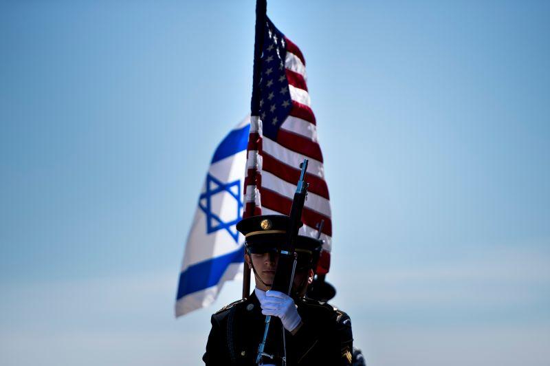 Members of the U.S. military carry the Israeli and U.S. flags.