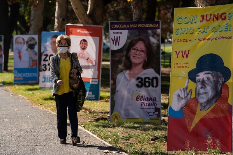 A woman walks past electoral posters ahead of this weekend's elections in Santiago, on May 12.