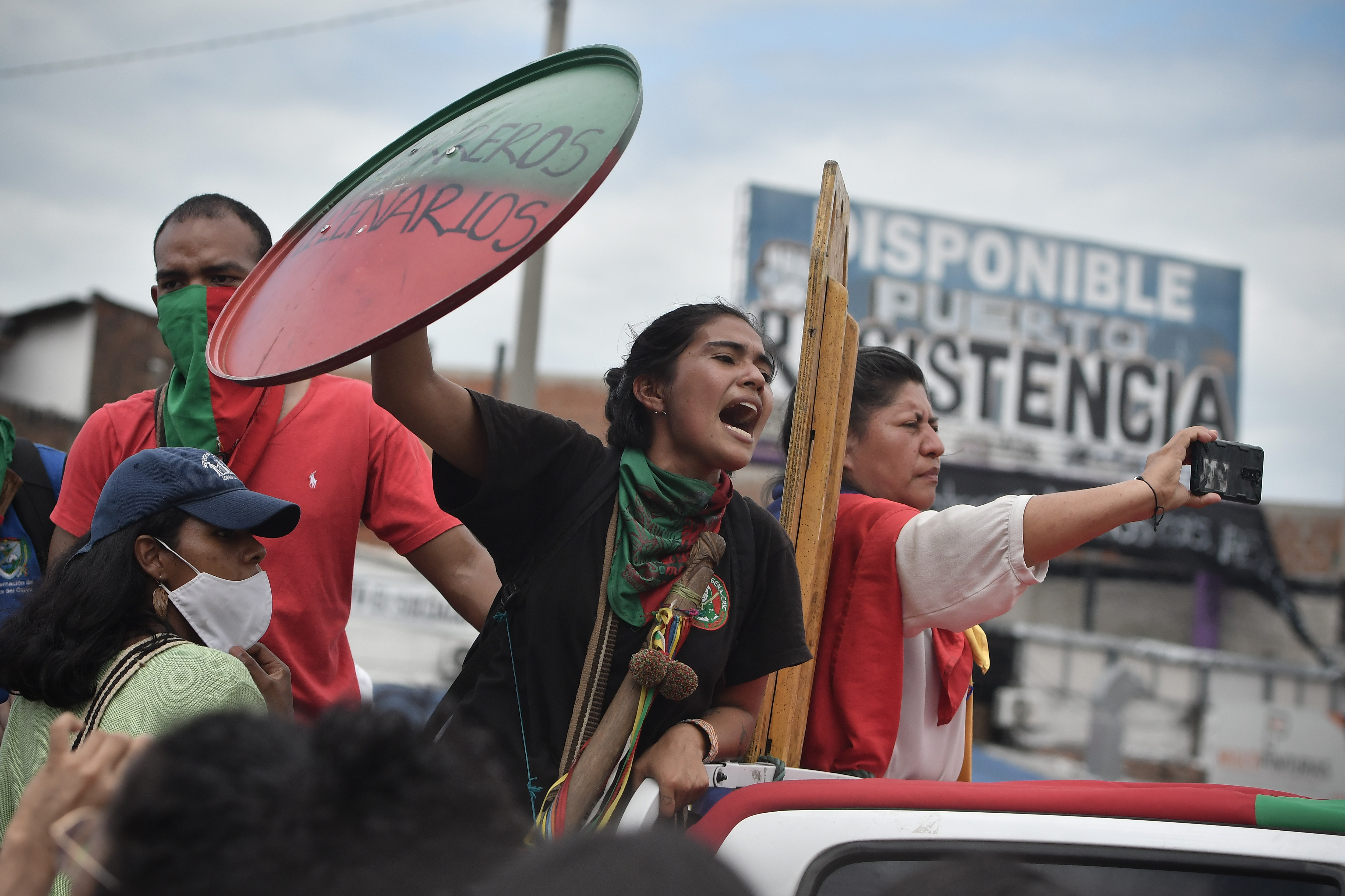 Protestors hold a makeshift shield and signs during a national strike against President Ivan Duque's administration in Cali, Colombia on May 12.