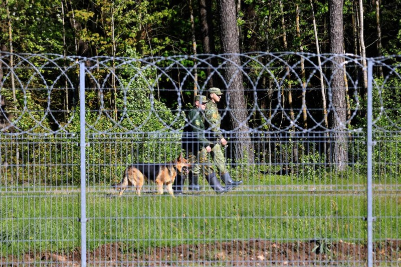 Belarus guards are seen patrolling a border fence during a protest by Reporters Without Borders against the detention of Belarus journalist Roman Protasevich at the Lithuanian-Belarus border in Salcininkai, Lithuania, on May 27.
