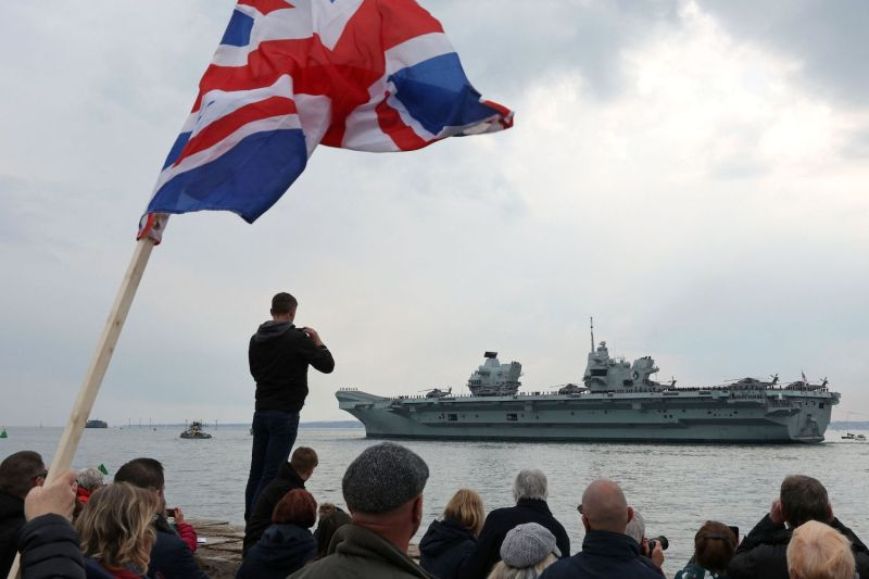 People watch from the shore as the HMS Queen Elizabeth aircraft carrier leaves Portsmouth Naval Base in southeastern England on May 1.