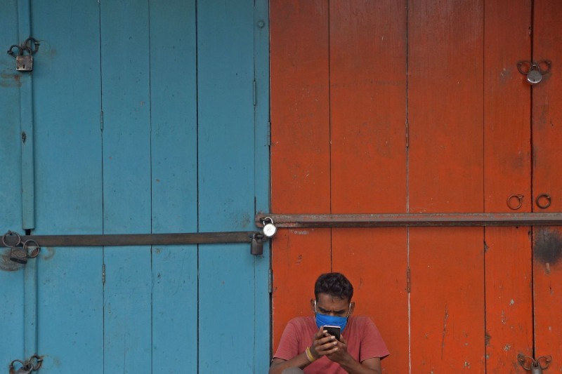 A man checks his mobile phone while sitting in front of a closed shop in West Bengal, India, on May 28.