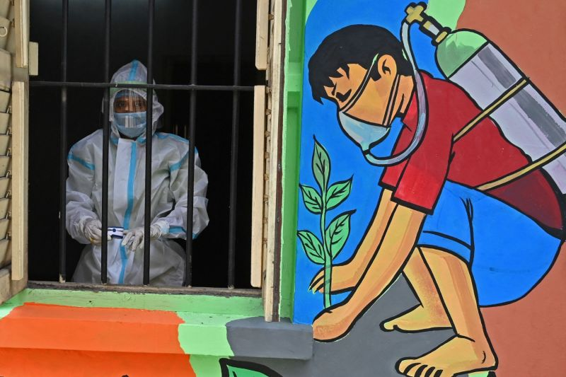 A health worker wearing a protective suit stands before a window in a newly inaugurated oxygen hub for COVID-19 patients in Kolkata, India, on May 23.