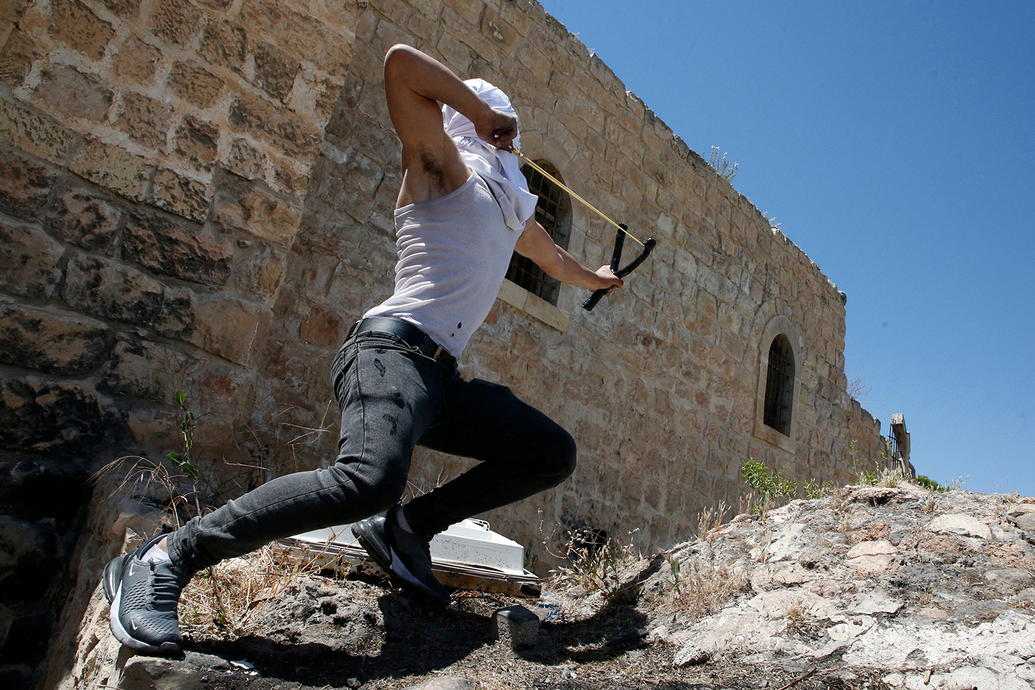 A Palestinian youth throws rocks