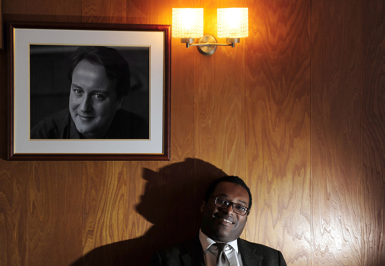 Kwasi Kwarteng under a portrait of David Cameron