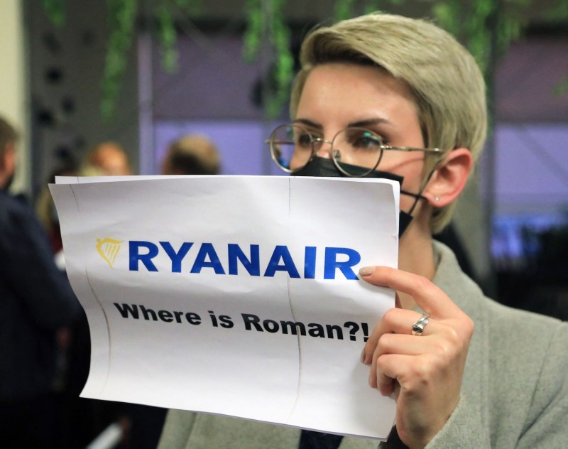 A woman holds a sign at Vilnius International Airport.