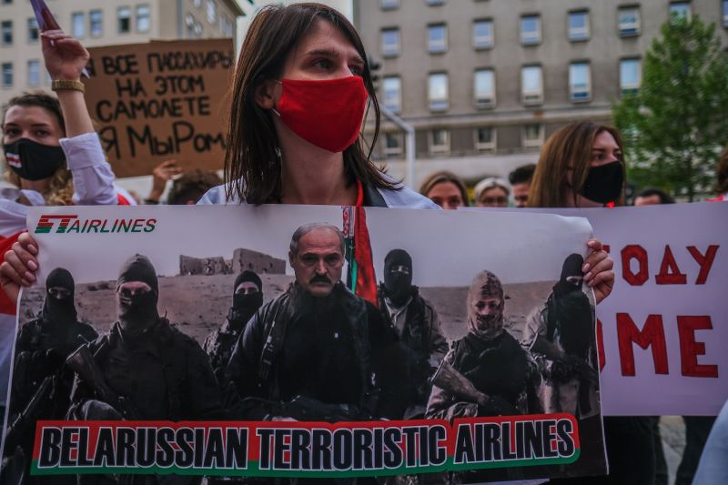 A woman holds a banner during a protest against the detention of the Belarusian journalist Roman Protasevich in front of the European Commission representative office on May 24, 2021 in Warsaw, Poland.