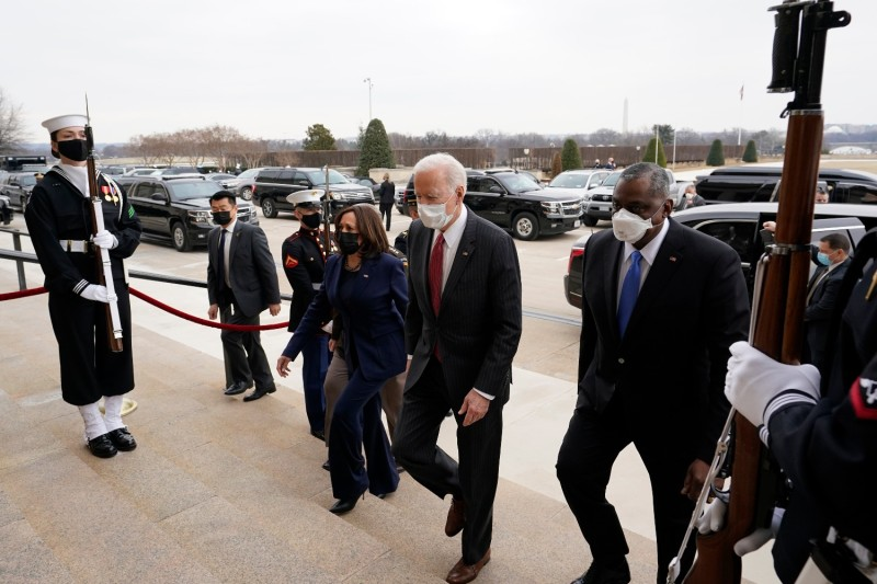 Biden, Harris, and others walk at the Pentagon.