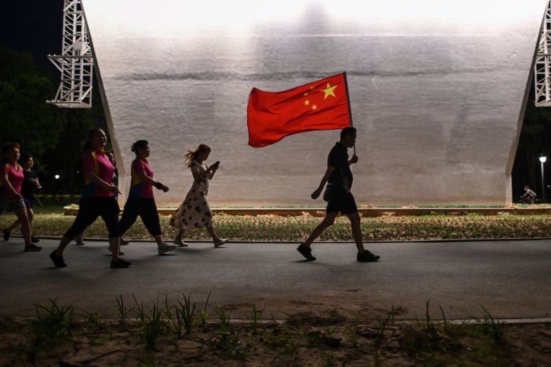 A man walks with the Chinese national flag in a park next to the Yangtze River in Wuhan, China, on Sept. 4, 2020.