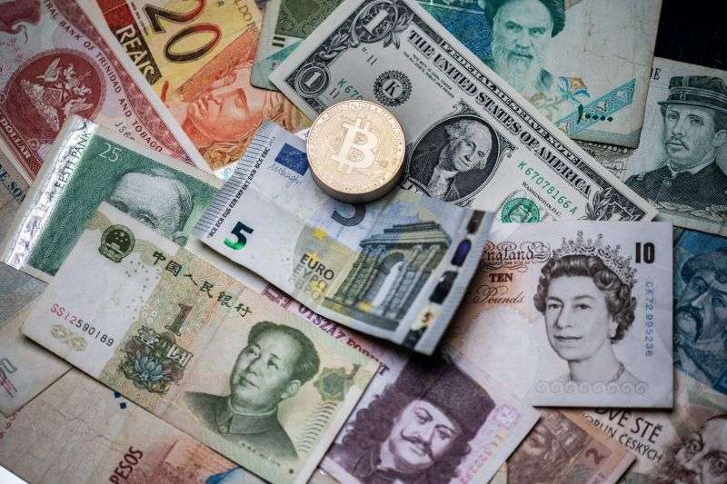 A physical imitation of the Bitcoin cryptocurrency is displayed on foreign bank notes.