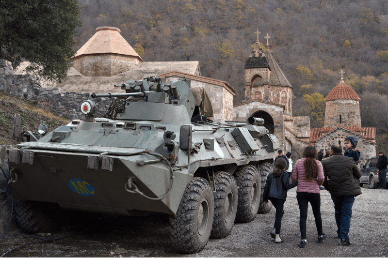 Armenians walk past an armored personnel carrier of Russian peacekeepers to visit the Dadivank monastery on the outskirts of Kalbajar in Nagorno-Karabakh on Nov. 18, 2020. The territory has since been transferred to Azerbaijan.