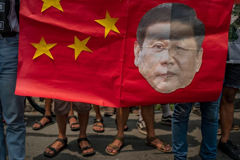 Filipinos hold a mock Chinese flag with a collage of the faces of Philippine President Rodrigo Duterte and Chinese President Xi Jinping during an anti-China protest in Manila on July 12, 2019.