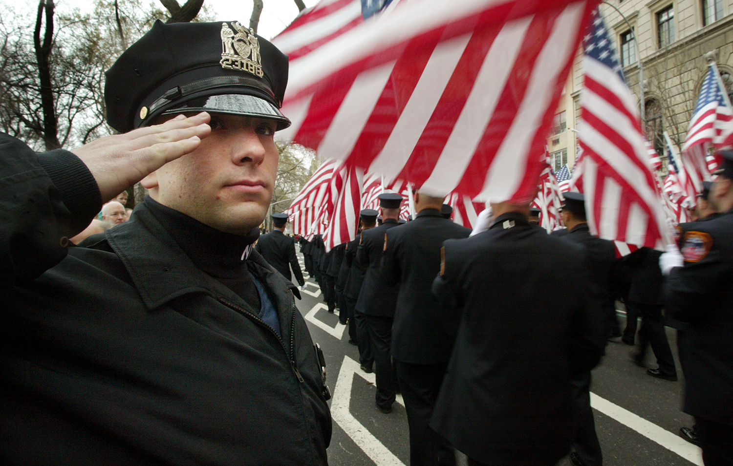A New York City police officer salutes firefighters as they march in the annual St. Patricks Day parade in New York on March 16, 2002.