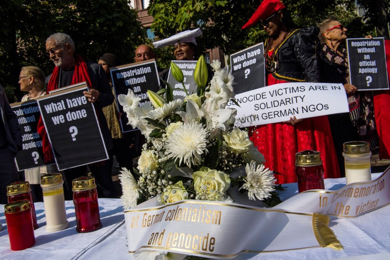 Demonstrators display placards and banners outside the venue where a handing-over ceremony takes place for human remains that were brought to Germany during its colonial rule of Namibia in Berlin on Aug. 29, 2018.