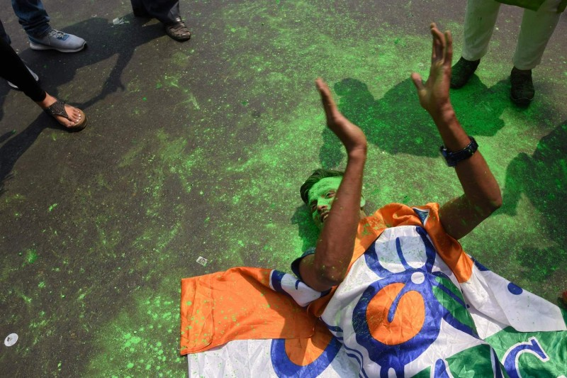 A supporter of All India Trinamool Congress party celebrates his party's electoral lead.