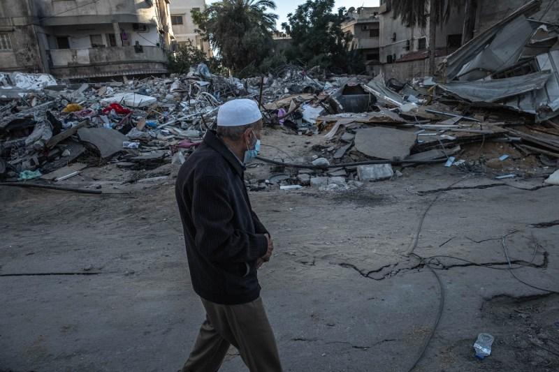 A Palestinian man walks beside rubble in Gaza.