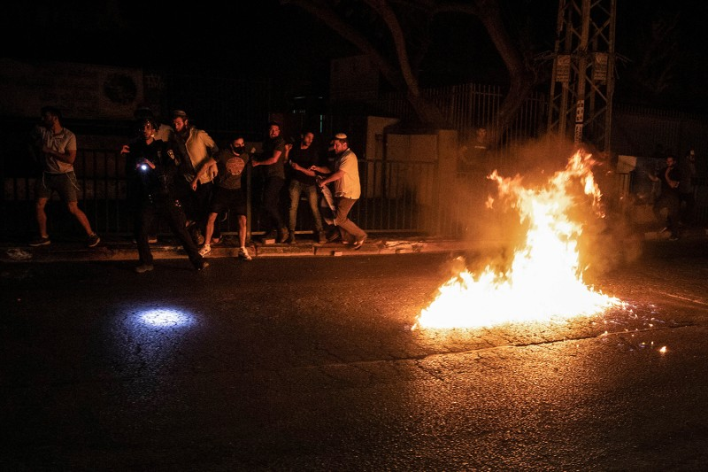 Arabs throw Molotov cocktails at Jewish right-wing protesters during clashes amid a nighttime curfew in the mixed Israeli-Arab city of Lod on May 12. Oren Ziv/picture alliance via Getty Images