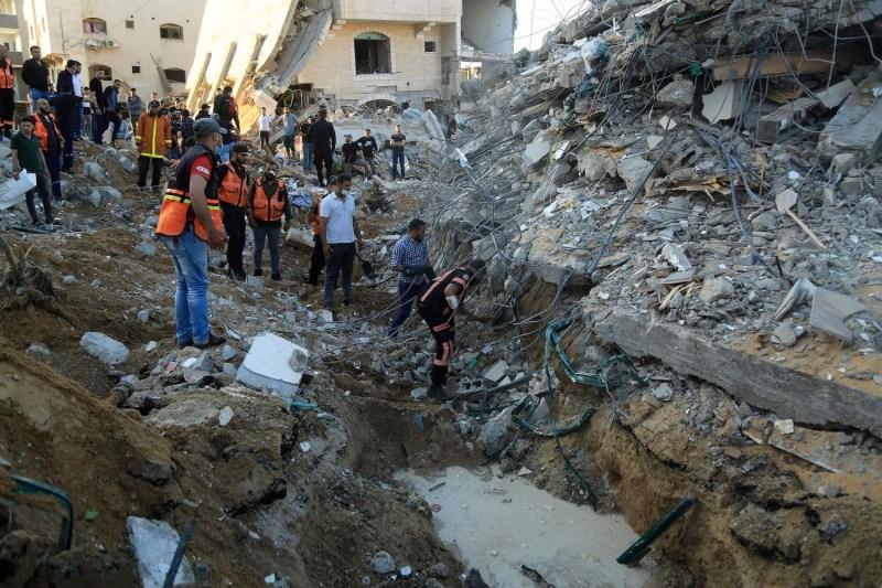 Palestinian paramedics search through rubble.