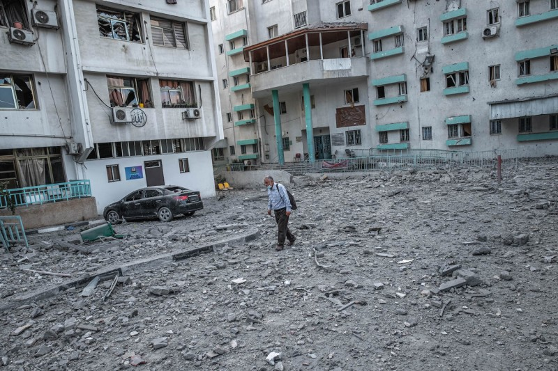 People inspect the rubble of a destroyed commercial building in Gaza.