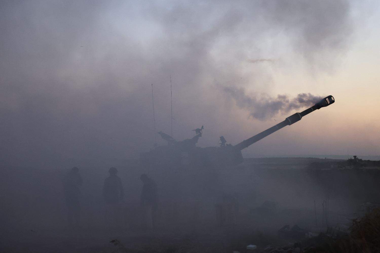Israeli soldiers fire toward the Gaza Strip.