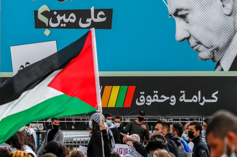 """A demonstrator holds a Palestinian flag near an electoral billboard for the predominantly Arab Israeli electoral alliance, the Joint List, depicting Israeli prime minister Benjamin Netanyahu with a caption reading in Arabic """"whom is he fooling?"""" in the mostly Arab city of Umm al-Fahm in northern Israel on March 12."""