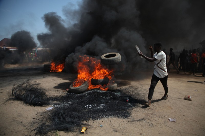A man throws a tire into a bonfire on the Kaduna-Abuja highway during a protest against kidnapping and killing in Gauraka, Nigeria, on May 24.