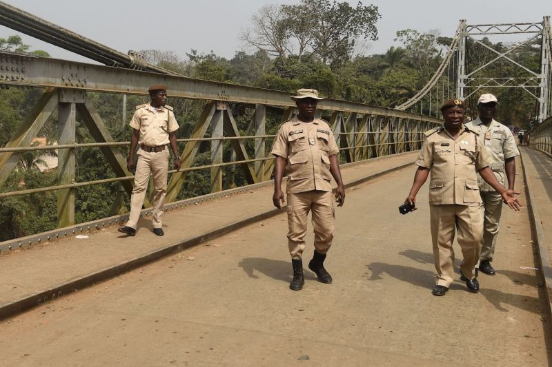 Immigration officers walk on a bridge built in 1948 that connects Nigeria with Cameroon at Mfum border station in Cross Rivers State, southeast Nigeria on February 1, 2018.