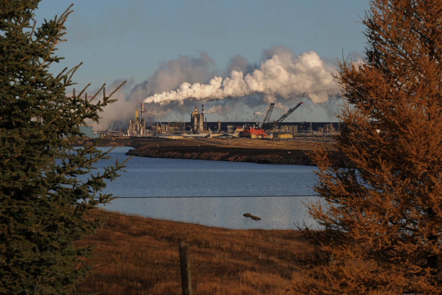 The Syncrude oil sands extraction facility is behind a lake in Alberta.