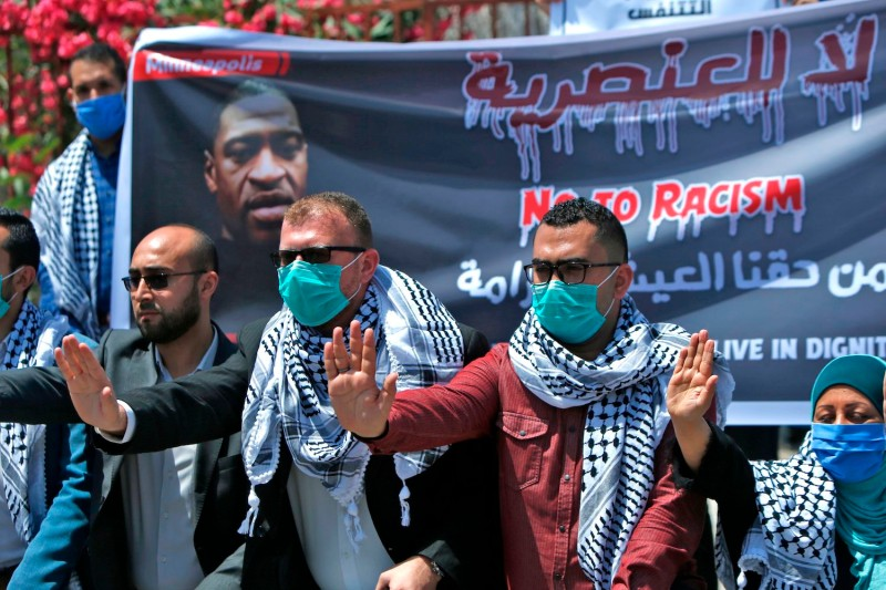 Palestinians in Gaza lift a banner protesting the killing of Eyad al-Hallaq and George Floyd.